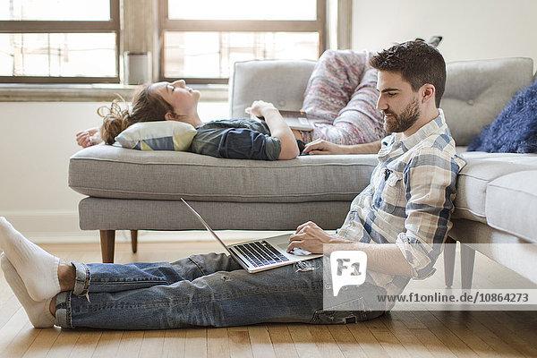 Junges Paar entspannt sich zu Hause  junge Frau schläft auf dem Sofa  junger Mann benutzt Laptop