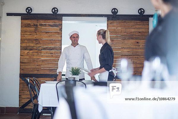 Kellnerin und Koch unterhalten sich im Restaurant