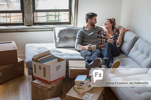 Umzug: Junges Paar entspannt auf Sofa  umgeben von Pappkartons