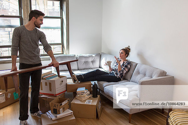 Moving house: Young woman relaxing on sofa while young man organises room