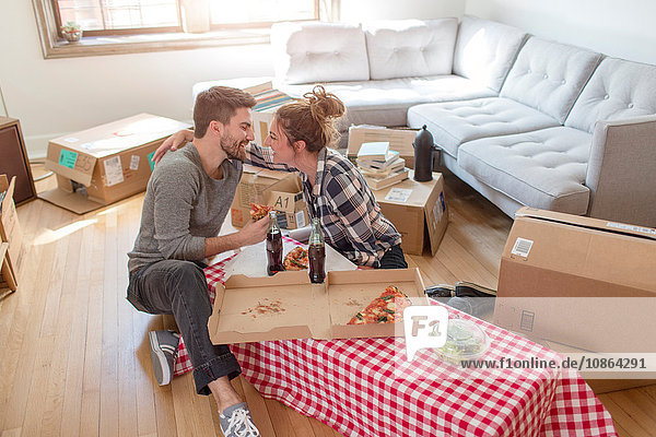 Moving house: Young couple eat pizza and hugging  in new home  surrounded by boxes