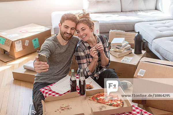 Moving house: Young couple taking self portrait with smartphone  in new home  surrounded by boxes