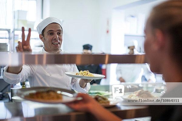 Kellnerin  die das Essen für den Kunden von der Küchentheke nimmt