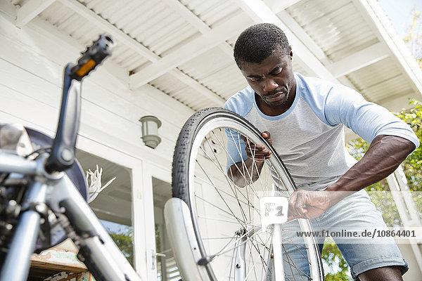 Mann befestigt Fahrrad in Veranda