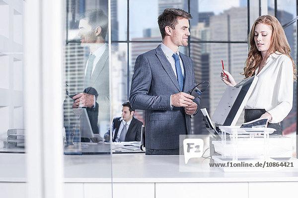Geschäftsmann und Geschäftsfrauen unterhalten sich per Fotokopierer im Büro  Kollegen am Computer im Hintergrund