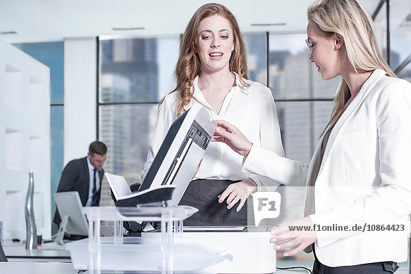 Businesswomen chatting by photocopier in office  colleagues using computer in background