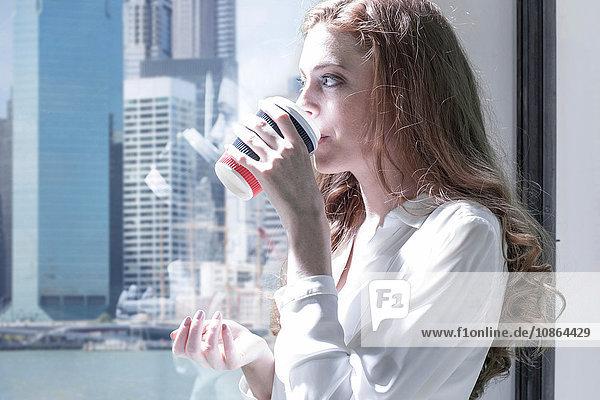 Geschäftsfrau schaut durch Fenster auf Kaffeepause im Büro