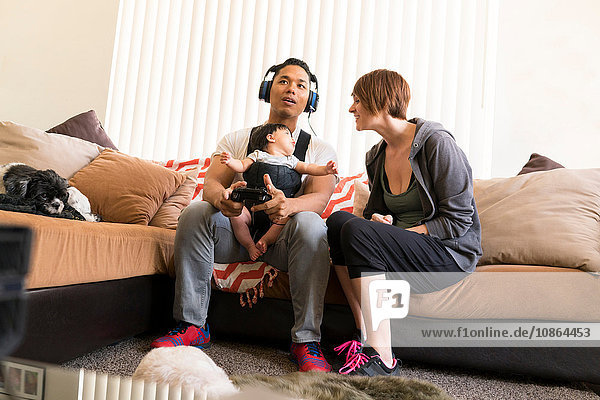 Mother beside father with baby in carrier  playing video game