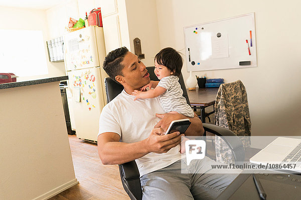 Vater benutzt Mobiltelefon und trägt Baby auf dem Arm