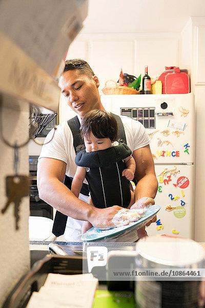 Vater mit Baby in Tragesitz  Geschirrspülen