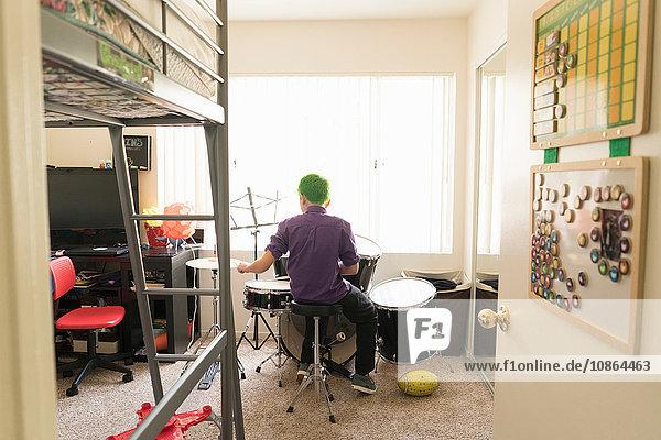 Junge spielt Schlagzeug im Schlafzimmer