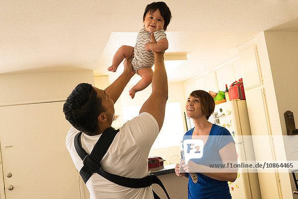 Mutter beobachtet Vater beim Heben des Kindes in der Luft