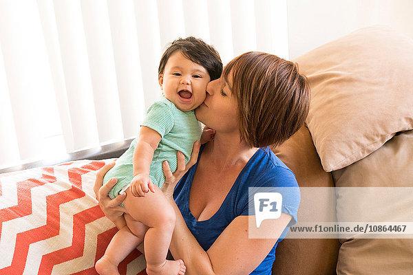 Mutter sitzt auf dem Sofa und küsst Babys Wange