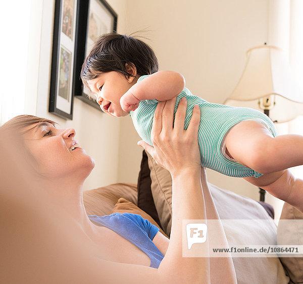 Mutter sitzt auf Sofa und hebt Baby in der Luft