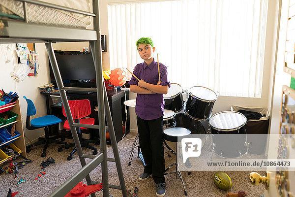 Junge posiert neben Trommeln im Schlafzimmer