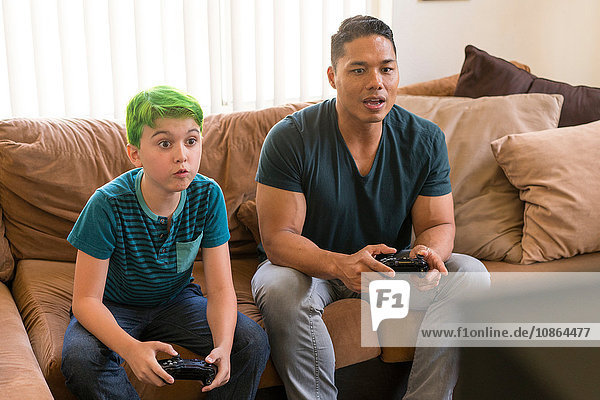 Father and son playing video game on sofa
