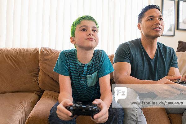 Vater und Sohn spielen Videospiel auf dem Sofa