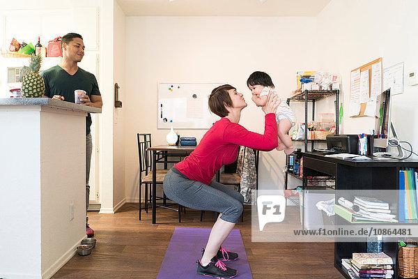 Vater beobachtet Mutter bei Kniebeugen mit Baby im Arm