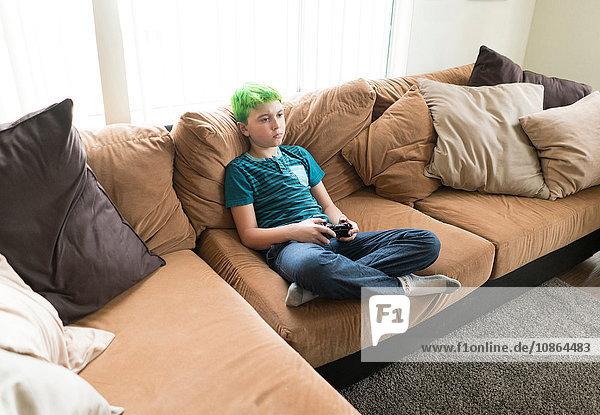 Junge spielt Videospiel auf dem Sofa