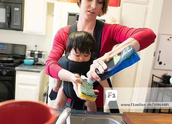 Mutter mit Baby in Tragesitz  Geschirrspülen