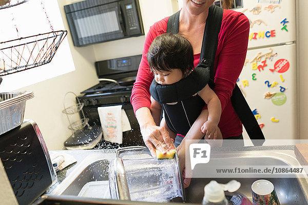 Mutter mit Baby in Tragesitz,  Geschirrspülen