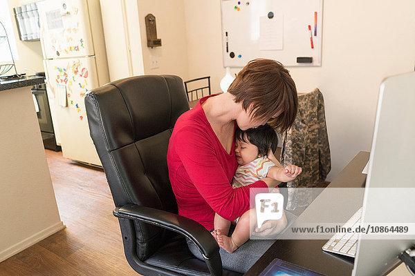 Mutter wiegt schlafendes Baby am Arbeitstisch