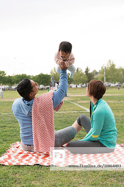 Couple playing with baby in park