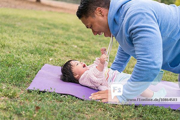 Vater trainiert mit Baby im Park