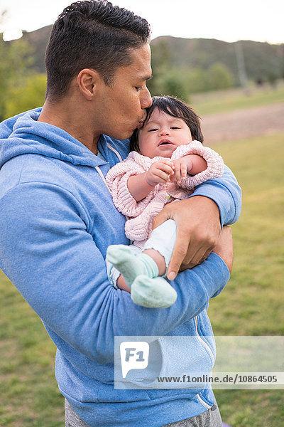 Vater wiegt und küsst Baby im Park