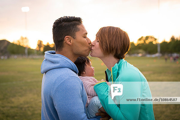 Couple with baby  kissing in park