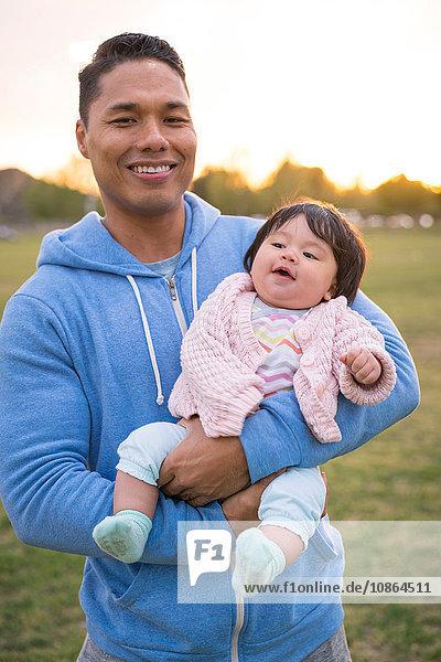 Vater wiegt Baby im Park