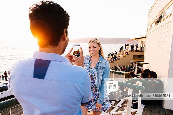 Junger Mann fotografiert Freundin in der Dämmerung mit Smartphone am Pier  Santa Monica  Kalifornien  USA