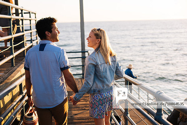 Rückansicht eines jungen Paares beim Spaziergang am Pier  Santa Monica  Kalifornien  USA