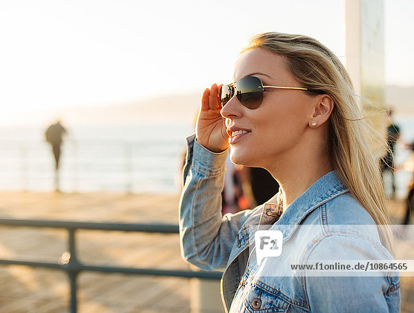 Young blond woman on sunlit pier,  Santa Monica,  California,  USA