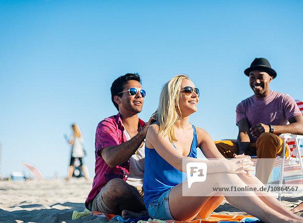 Junger Mann trägt Sonnencreme auf die Schultern von Freunden am Strand auf  Santa Monica  Kalifornien  USA