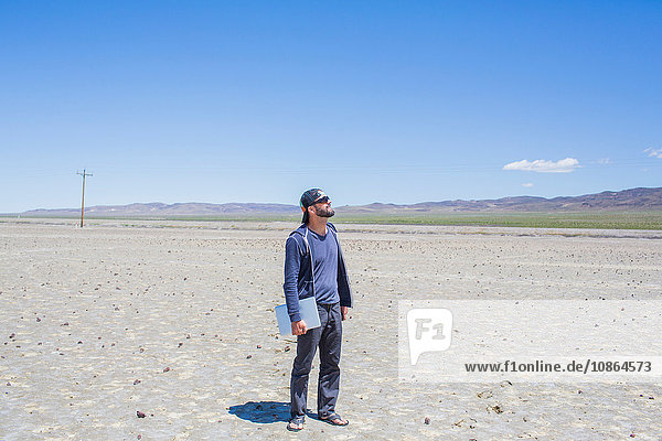 Man standing in desert holding laptop looking up  Nevada  USA