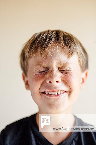 Studioporträt eines Jungen mit geschlossenen Augen und zahnartigem Lächeln