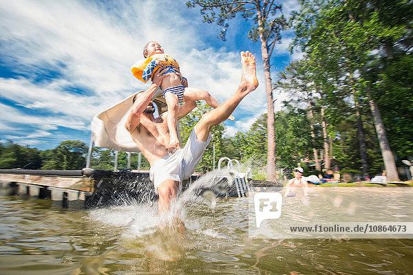 Mann hält seine Tochter auf,  die am Jackson Lake,  Georgia,  USA,  von einer Rutsche springt