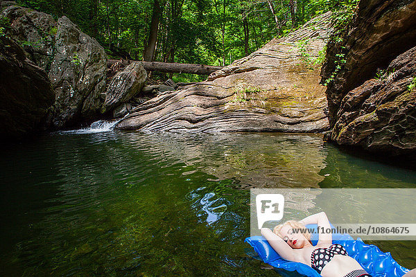 Woman relaxing on inflatable  in lake  Devil's Pool  Wissahickon Park  Philadelphia  U.S.A