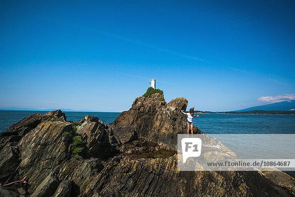 Junge Frau springt auf Felsen am Ozean  Bowen Island  Britisch-Kolumbien  Kanada Junge Frau springt auf Felsen am Ozean, Bowen Island, Britisch-Kolumbien, Kanada