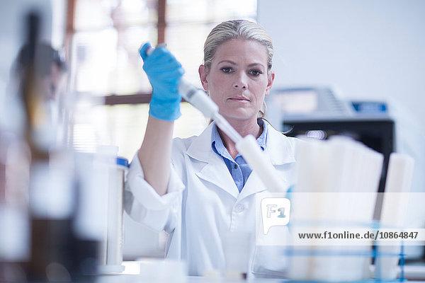 Mittlere erwachsene Frau beim Einführen eines Reagenzglases im Labor