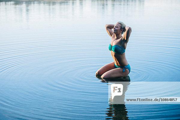 Woman wearing bikini kneeling in water