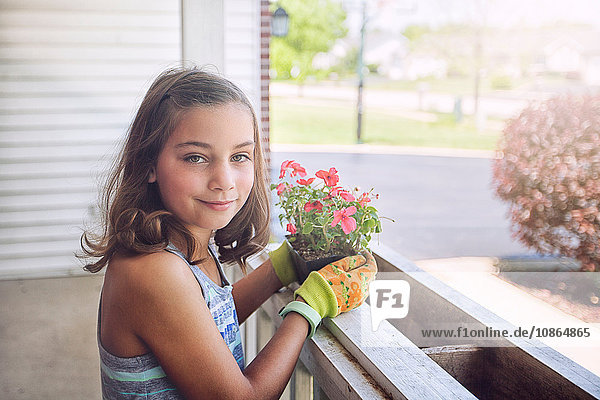 Girl planting flowers in planter box  looking at camera smiling