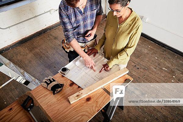 Zimmermann schaut sich mit dem Kunden den Bauplan an