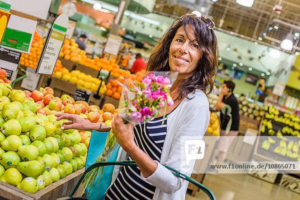 Frau im Supermarkt mit Blumenstrauss