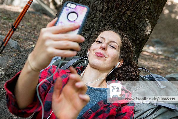 Young female hiker taking smartphone selfie in forest  Arcadia  California  USA