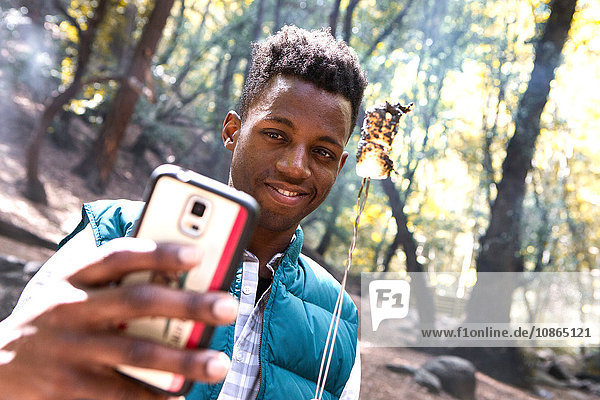 Young male hiker taking smartphone selfie with toasted marshmallow in forest  Arcadia  California  USA