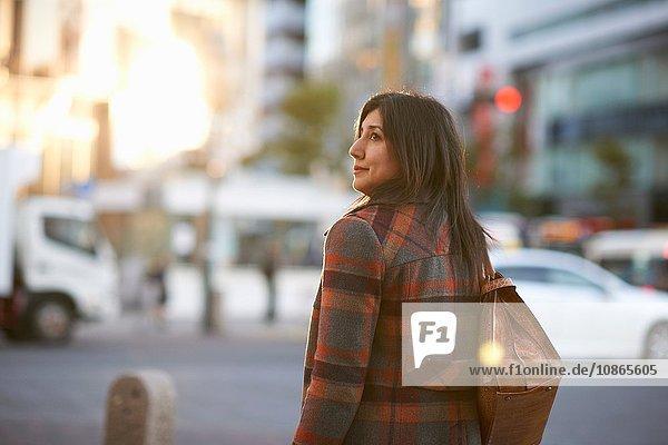 Rückansicht einer reifen Frau in der Stadt  die eine Handtasche auf der Schulter trägt und zur Seite schaut  Shibuya  Tokio  Japan