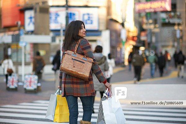 Rückansicht einer reifen Frau in der Stadt  die mit Einkaufstüten Einkaufstaschen über einen Fußgängerüberweg trägt und zur Seite schaut  Shibuya  Tokio  Japan