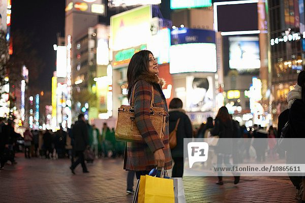 Side view of mature woman carrying handbag and shopping bags in city at night looking up smiling,  Shibuya,  Tokyo,  Japan